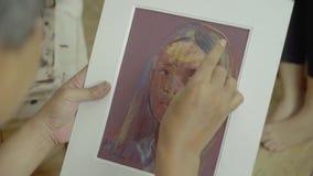 Τα αρσενικά χέρια ζωγράφων κάνουν μια ζωγραφική γυναικών απόθεμα βίντεο