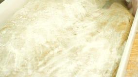 Τα αρσενικά χέρια που ζυμώνουν τη ζύμη στο αλεύρι, προετοιμάζουν τη ζύμη για το ψήσιμο φιλμ μικρού μήκους
