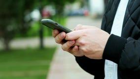 Τα αρσενικά χέρια που κρατούν το σύγχρονο κινητό τηλέφωνο, άτομο δακτυλογραφούν sms, να κουβεντιάσουν απόθεμα βίντεο