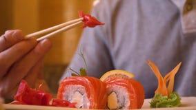 Τα αρσενικά χέρια που παίρνουν την κόκκινη πιπερόριζα με ξύλινα chopsticks τρώγοντας τα σούσια κυλούν απόθεμα βίντεο