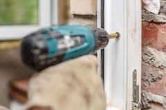 Τα αρσενικά χέρια που χρησιμοποιούν ένα ηλεκτρικό κατσαβίδι και οι βίδες πρόκειται να στερεώσουν ένα πλαίσιο παραθύρων PVC σε ένα στοκ εικόνα με δικαίωμα ελεύθερης χρήσης