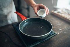 Τα αρσενικά χέρια προσώπων χύνουν το πετρέλαιο σε ένα τηγανίζοντας τηγάνι Στοκ Φωτογραφίες