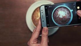Τα αρσενικά χέρια στο smartphone παίρνουν μια εικόνα του σχεδίου σε έναν frothy καφέ απόθεμα βίντεο