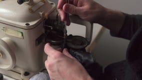 Τα αρσενικά χέρια του ράφτη ράβουν τη γούνα furrier στη μηχανή απόθεμα βίντεο