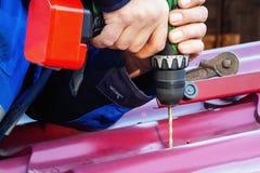 Τα αρσενικά χέρια τρυπούν μια τρύπα στη στέγη για τη βίδα με ένα κατσαβίδι με τρυπάνι Επισκευή στεγών στοκ φωτογραφίες με δικαίωμα ελεύθερης χρήσης
