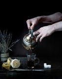 Τα αρσενικά χέρια χύνουν το τσάι στο διαφανές φλυτζάνι σκοτεινό υπόβαθρο, τρύγος Στοκ Φωτογραφίες