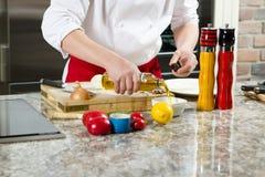 Τα αρσενικά χέρια χύνουν το φυτικό έλαιο σε ένα πιάτο Στοκ εικόνα με δικαίωμα ελεύθερης χρήσης