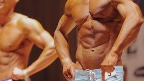 Τα αρσενικά bodybuilders που παίρνουν το μπροστινό lat που διαδίδεται θέτουν, θέτοντας στη σκηνή, αθλητικός διαγωνισμός απόθεμα βίντεο