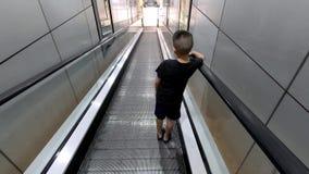 Τα ασιατικά αγόρια στην κυλιόμενη σκάλα κινούνται κάτω φιλμ μικρού μήκους