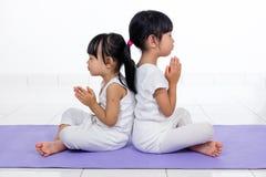 Τα ασιατικά κινεζικά μικρά κορίτσια που ασκούν τη γιόγκα θέτουν Στοκ Εικόνα