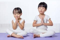 Τα ασιατικά κινεζικά μικρά κορίτσια που ασκούν τη γιόγκα θέτουν Στοκ εικόνα με δικαίωμα ελεύθερης χρήσης