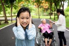 Τα ασιατικά κλειστά κόρη αυτιά με τα χέρια, λίγο κορίτσι παιδιών δεν θέλησαν να ακούσουν τους γονείς, τη γιαγιά στην αναπηρική κα στοκ εικόνες