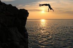 Τα ασιατικά κορίτσια πηδούν από έναν απότομο βράχο στο ηλιοβασίλεμα επεισοδίου θάλασσας, κάνουν τούμπα στον ωκεανό Στοκ Εικόνα