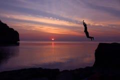 Τα ασιατικά κορίτσια πηδούν από έναν απότομο βράχο στο ηλιοβασίλεμα επεισοδίου θάλασσας Στοκ Εικόνες