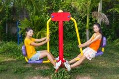 Τα ασιατικά ταϊλανδικά κορίτσια με τη μηχανή άσκησης σταθμεύουν δημόσια Στοκ εικόνα με δικαίωμα ελεύθερης χρήσης