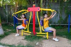 Τα ασιατικά ταϊλανδικά κορίτσια με τη μηχανή άσκησης σταθμεύουν δημόσια Στοκ Φωτογραφία