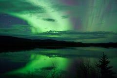 Τα αστέρια νυχτερινού ουρανού καλύπτουν τα βόρεια φω'τα που αντανακλώνται στοκ φωτογραφία
