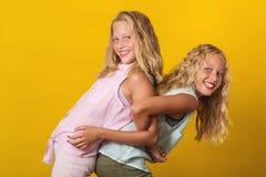 Τα αστεία δίδυμα κοριτσιών έχουν τη διασκέδαση μαζί στο κίτρινο υπόβαθρο στοκ φωτογραφία με δικαίωμα ελεύθερης χρήσης