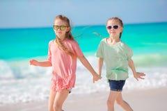 Τα λατρευτά μικρά κορίτσια έχουν τη διασκέδαση μαζί στην άσπρη τροπική παραλία Στοκ εικόνες με δικαίωμα ελεύθερης χρήσης