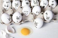 Τα αυγά κοτών στο κιβώτιο Κάλυψη αυγών με τα σχέδια Μοιάστε με το πρόσωπο ατόμων Τα Indignant αυγά εξετάζουν το σπασμένο αυγό Στοκ Φωτογραφίες