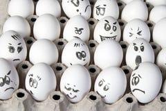 Τα αυγά κοτών στο κιβώτιο Κάλυψη αυγών με τα σχέδια Μοιάστε με το πρόσωπο ατόμων Στοκ εικόνες με δικαίωμα ελεύθερης χρήσης