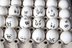 Τα αυγά κοτών στο κιβώτιο Κάλυψη αυγών με τα σχέδια Μοιάστε με το πρόσωπο ατόμων Στοκ Εικόνες