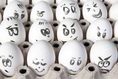 Τα αυγά κοτών στο κιβώτιο Κάλυψη αυγών με τα σχέδια Μοιάστε με το πρόσωπο ατόμων Στοκ εικόνα με δικαίωμα ελεύθερης χρήσης