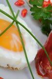 τα αυγά μπέϊκον τηγάνισαν δευτερεύοντα ηλιόλουστο επάνω πρασίνων Στοκ φωτογραφία με δικαίωμα ελεύθερης χρήσης