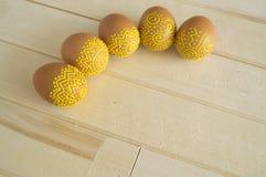 Τα αυγά Πάσχας βρίσκονται σε έναν ξύλινο πίνακα Χρωματισμένα καφετιά αυγά Στοκ Φωτογραφία