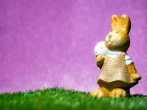 Τα αυγά Πάσχας λαβής κουνελιών Πάσχας στην πράσινη χλόη το υπόβαθρο είναι βασιλική πορφύρα Έννοια Πάσχας, διάστημα αντιγράφων Στοκ φωτογραφία με δικαίωμα ελεύθερης χρήσης