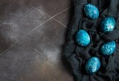 Τα αυγά Πάσχας που χρωματίζονται κοντά παραδίδουν το μπλε χρώμα στο σκοτεινό υπόβαθρο Στοκ Εικόνες