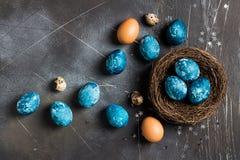 Τα αυγά Πάσχας στη φωλιά που χρωματίζεται κοντά παραδίδουν το μπλε χρώμα στο σκοτεινό υπόβαθρο στοκ φωτογραφία με δικαίωμα ελεύθερης χρήσης