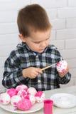 Τα αυγά Πάσχας χρωμάτων αγοριών Στοκ Εικόνες