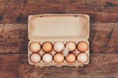 Τα αυγά στα κιβώτια χαρτοκιβωτίων που βάζουν στην ξύλινη αναδρομική τοπ άποψη Στοκ Φωτογραφίες