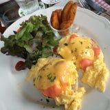 Τα αυγά Benedict με την καπνισμένη κορυφή σολομών με τα φρέσκα χορτάρια και η σάλτσα εξυπηρετούν με την πράσινες σαλάτα και τις τ Στοκ Εικόνες