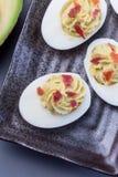 Τα αυγά Deviled γέμισαν με το αβοκάντο, το λέκιθο αυγών και γεμίζοντας μαγιονέζας, που διακοσμήθηκαν με το μπέϊκον, κάθετη, τοπ ά στοκ φωτογραφία με δικαίωμα ελεύθερης χρήσης