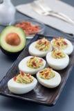 Τα αυγά Deviled γέμισαν με το αβοκάντο, το λέκιθο αυγών και την πλήρωση μαγιονέζας που διακοσμήθηκαν με το μπέϊκον, κάθετο στοκ φωτογραφία