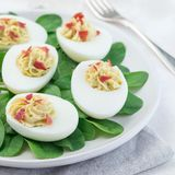 Τα αυγά Deviled γέμισαν με το αβοκάντο, το λέκιθο αυγών και την πλήρωση μαγιονέζας, που διακοσμήθηκαν με το μπέϊκον στα φύλλα σπα στοκ φωτογραφίες με δικαίωμα ελεύθερης χρήσης
