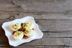 Τα αυγά Deviled σε ένα λευκό καλύπτουν και στο παλαιό ξύλινο υπόβαθρο με την κενή θέση για το κείμενο βρασμένα αυγά σκληρά Στοκ φωτογραφία με δικαίωμα ελεύθερης χρήσης