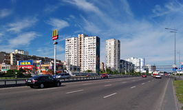 Τα αυτοκίνητα οδηγούν κατά μήκος του πεζοδρομίου του Κίεβου, στο οποίο υπάρχουν καταστήματα και σπίτια διαμερισμάτων Στοκ εικόνα με δικαίωμα ελεύθερης χρήσης