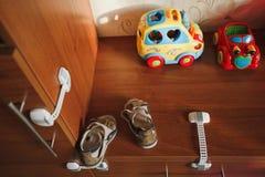 Τα αυτοκίνητα παιχνιδιών παιδιών ` s, παπούτσια παιδιών ` s είναι σε ένα ξύλινο ράφι Εδώ κοντά υπάρχει μια ντουλάπα με τα βουλώμα Στοκ εικόνα με δικαίωμα ελεύθερης χρήσης