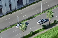 Τα αυτοκίνητα πηγαίνουν οδικώς στην οδό πόλεων που διαιρείται με τα πράσινα διαστήματα και τους φοίνικες Στοκ φωτογραφία με δικαίωμα ελεύθερης χρήσης