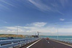 Τα αυτοκίνητα πηγαίνουν στην της Κριμαίας γέφυρα πέρα από το στενό Kerch Στο αριστερό είναι η κατασκευή της γέφυρας σιδηροδρόμων στοκ εικόνα