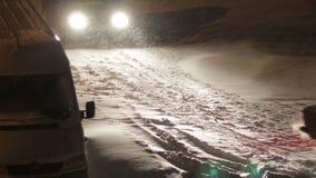 Τα αυτοκίνητα πηγαίνουν στη νύχτα το χειμώνα στο χιόνι απόθεμα βίντεο