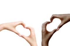 Τα αφρικανικά και άσπρα θηλυκά χέρια παρουσιάζουν καρδιά στο άσπρο υπόβαθρο Στοκ Εικόνες