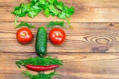 Τα λαχανικά κατωφλιών, οι ντομάτες, το αγγούρι, το πιπέρι τσίλι και τα χορτάρια με μορφή των ατόμων διευθύνουν στο ξύλινο υπόβαθρ Στοκ φωτογραφία με δικαίωμα ελεύθερης χρήσης