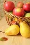 Τα αχλάδια σε έναν ξύλινο πίνακα και τα μήλα είναι σε ένα trug στοκ φωτογραφίες