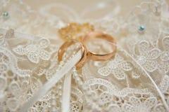 Τα δαχτυλίδια στα λουλούδια, σε ένα κιβώτιο, σε ένα άσπρο ύφασμα στα παιχνίδια, χρώματα, γαμήλιες λεπτομέρειες, γαμήλια δαχτυλίδι Στοκ Εικόνα