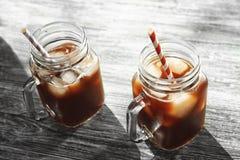 Τα βάζα του Mason με το κρύο παρασκευάζουν τον καφέ και τα άχυρα στοκ φωτογραφίες
