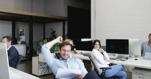Τα βέβαια επιχειρησιακά τεθειμένα άτομο πόδια στο γραφείο, ρίχνουν μακριά τα έγγραφα που έχουν το υπόλοιπο, οκνηρός αρσενικός διε φιλμ μικρού μήκους